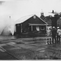 Removal of the B. and M. Freight House by Burning and as a Fire Fighter's Training Exercise. 7/12/1975. Neighboring Buildings Safe Behind Water Fans.